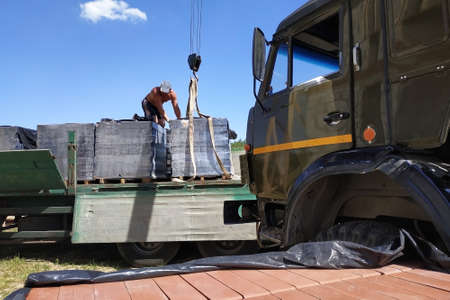 Workers unload pallets with bricks by means of the crane of automobile. 2019