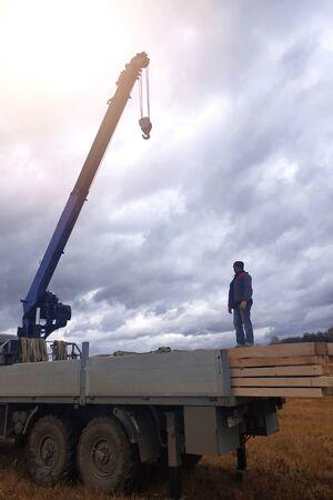 Photo pour The crane lowers the roof construction boards.2020 - image libre de droit