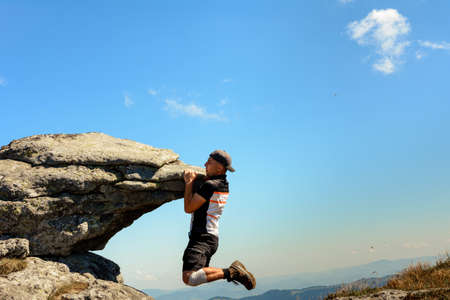 Photo for Tourist climber makes a climb on a large rocky rock without protection, the Ukrainian Carpathians, danger and extreme. 2020 - Royalty Free Image