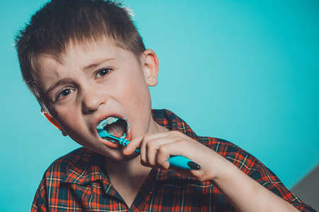 Photo pour Daily oral hygiene procedure, the boy follows the rules of cleanliness and oral hygiene. A boy brushing his teeth in disgust and grimacing at toothpaste. - image libre de droit