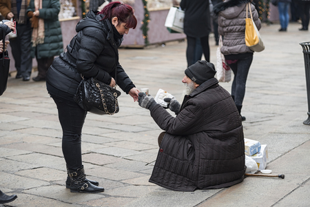 Photo for Milan Italy 12142015: Milan as the other big cityes in the world presents big contrasts between the richness and the joy for the holidays and chrismats the poorness of the tramps asking alms. - Royalty Free Image