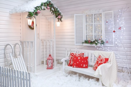 Foto de Winter exterior of a country house with Christmas decorations in the American style. Snow-covered courtyard with a porch, tree, white bench and wooden vintage sleds. - Imagen libre de derechos