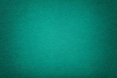 Foto de Dark turquoise matte background of suede fabric, closeup. Velvet texture of seamless green woolen felt with vignette. - Imagen libre de derechos