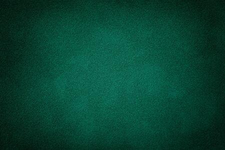 Foto de Dark green matte background of suede fabric, closeup. Velvet texture of seamless deep emerald leather. Felt material macro with vignette. - Imagen libre de derechos