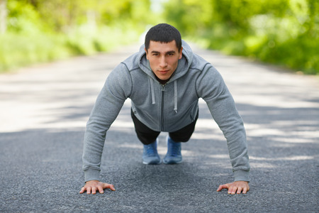 Fitness man exercising push ups, outdoor. Muscular male cross-training on city park