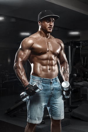 Handsome muscular man with dumbbells working out in gym, doing exercise