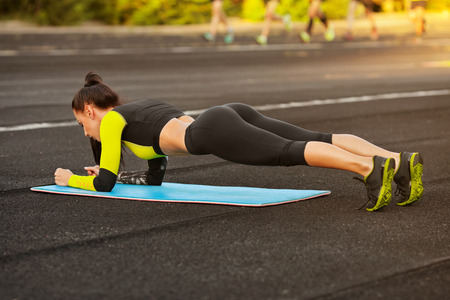 Slim athletic woman doing planking exercise in the stadium, sporty girl workout, outdoors