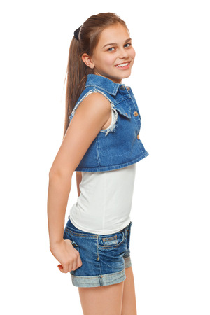 Stylish young girl in a jeans vest and denim shorts. Street style teenager, lifestyle, isolated on white backgroundの写真素材
