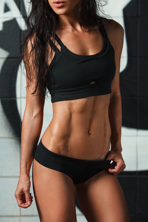 Photo pour Fitness sexy woman showing abs and flat belly. Beautiful muscular girl, shaped abdominal, slim waist - image libre de droit
