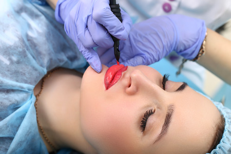 Photo pour Healthy Spa: Young Beautiful Woman Having Permanent Make-up Tattoo on her Lips. Close-up - image libre de droit