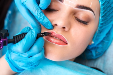 Photo for Cosmetologist making permanent makeup on womans face - Royalty Free Image