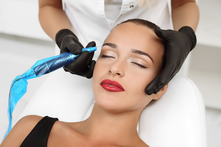 Foto de Cosmetologist applying permanent make up on eyebrows- eyebrow tattoo - Imagen libre de derechos