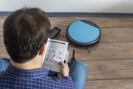 Photo pour Man sitting on the floor and reading instructions manual for a robot vacuum cleaner - image libre de droit