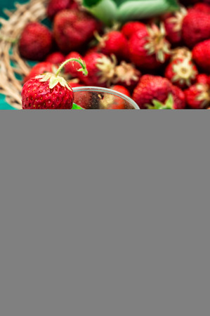 glass with drink of strawberries and mint on the background of the basket full berries.Selective focus.Photo tinted