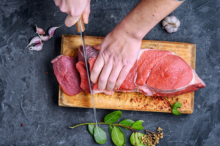 Man slicing beef stead on wooden cutting board