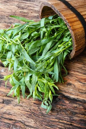 Tarragon herbs in wooden tub on a wooden background