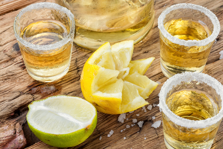 Photo pour Mexican gold tequila with lime and salt on old wooden table - image libre de droit