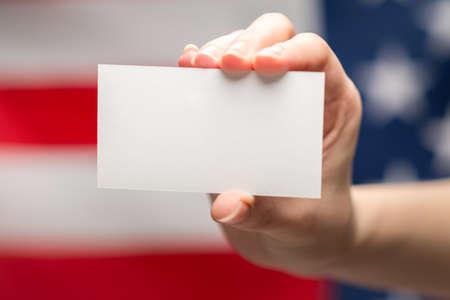 Photo pour Empty card in woman hand. Copy space. American flag background. - image libre de droit