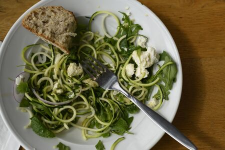 Spend free time in a cafe or restaurant, order and eat fresh, tasty and healthy food. In this photo we see a salad that can be ordered in a restaurant and it will be delicious and also very easy to make at home. The ingredients are simple, take zucchini, make pasta from it, then herbs, red onion and feta. She may be vegetarian. And it's all. We mix everything and sprinkle with fresh herbs and pour over the sauce. For example, olive oil. Bon Appetit. On this we see the half-eaten salad. Perhaps the person went to the toilet, or ate, or in a hurry. The concept of healthy and vitamin nutrition. Ideal for cafes, cafeterias and restaurants. It can serve as a motivational picture. Light composition on a wooden table. Horizontal view.