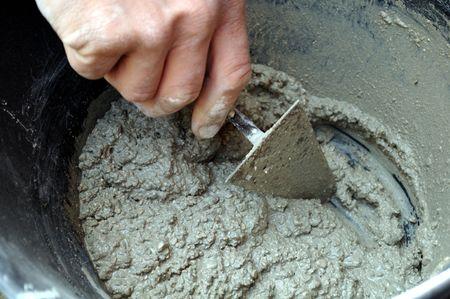 Detail of mason hand preparing cement