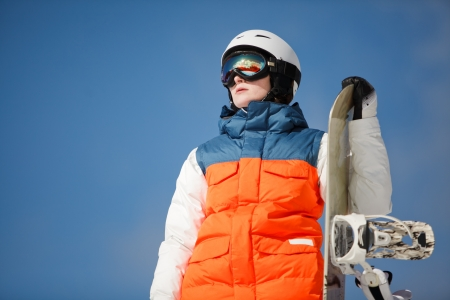 female snowboarder against sun and skyの写真素材