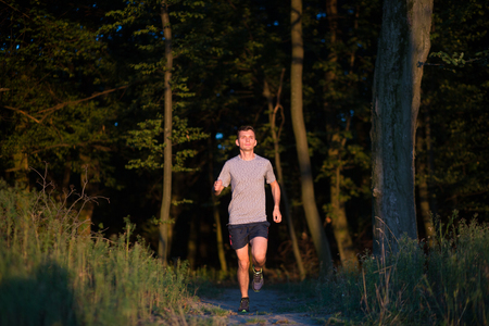 Sport running man in cross country trail run on sunset