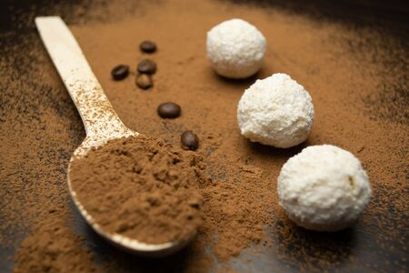 Photo pour Three white truffles, a wooden spoon with cocoa, coffee grains on a black background - image libre de droit