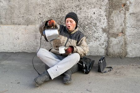 Photo for Homeless dirty woman sits under the wall and pours herself tea - Royalty Free Image