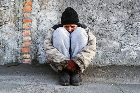 Photo for Dirty homeless woman sitting under a gray wall hugging her legs - Royalty Free Image
