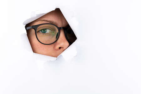 Photo for A woman's eye with black-framed glasses looks through a hole in a white paper wall. Espionage concept. Free space for text. - Royalty Free Image
