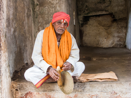 MELKOTE, INDIA - MAY 9th - A sadhu strikes his gong begging for alms in a rocky alcove on May 9th 2008 at Melkote, India.