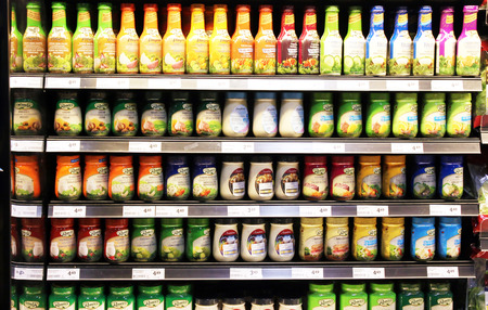 Variety of salad dressings on shelves in a supermarket