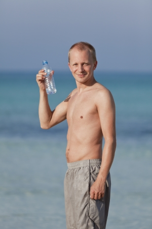 Young man boy drinking refreshing water from a bottle on the beach by the sea in summer vacation