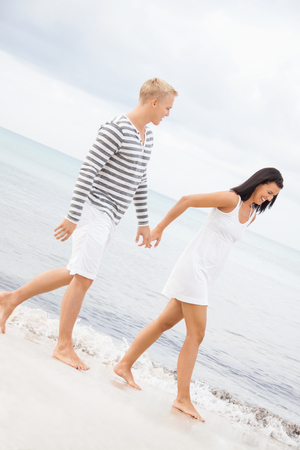 Caucasian happy young couple holding hands while walking barefoot on the beach in a romantic travel destination
