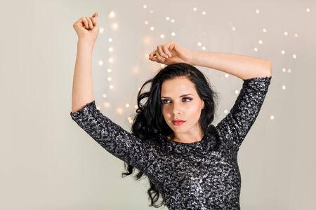 Beautiful dreamy woman with glitter dress dancing portrait party