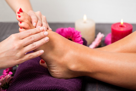 Woman having a pedicure treatment at a spa or beauty salon with the pedicurist massaging the soles of her feet with a pumice stone to cleanse dead skin and stimulate the tissue