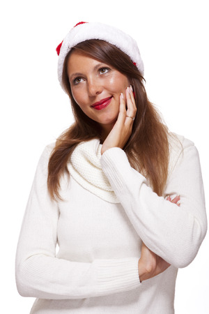 Attractive woman wearing a festive red Santa hat snuggling into her warm winter polo-neck sweater with a charming friendly smile, isolated on white