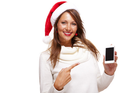 Pretty woman in a Santa hat reading a sms on her mobile phone sending Christmas wishes smiling with pleasure at the news, isolated on white