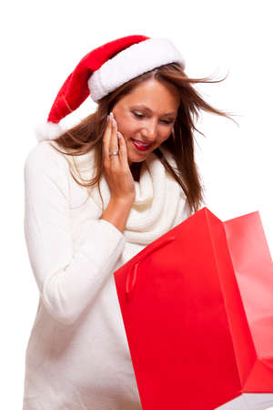 Happy vivacious Christmas shopper wearing a red Santa hat holding up a colorful red shopping bag with a beautiful beaming smile, isolated on white with copyspace