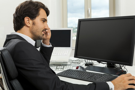 Stylish businessman in a suit sitting at his desk in the office chatting on the phone with a view of his blank computer monitor