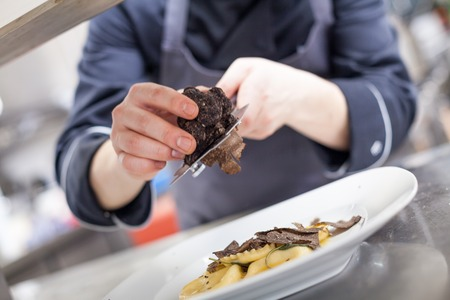 Photo pour Chef grating truffle mushroom shavings onto homemade ravioli in a restaurant kitchen while preparing a dinner, close up view of the counter, plate and hands - image libre de droit