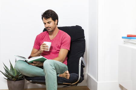 Young Man in Casual Clothing Sitting on Black Chair While Reading a Book and Holding a Glass of Drink.