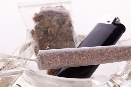 Close up of marijuana joint made with translucent rolling papers, plastic baggy of dried marijuana, black lighter and pipe on white background