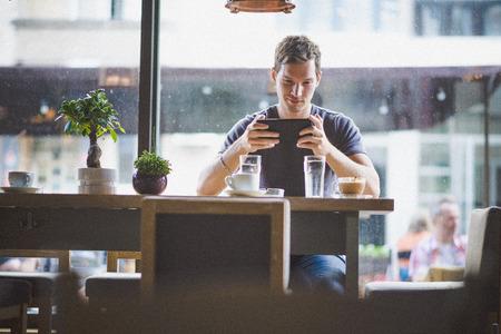 Photo pour Young man watching tablet in cafe - image libre de droit
