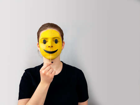 Photo pour Close up portrait young woman, teenage girl, face painted yellow as smiley, with black smile on stick instead of real lips, black T shirt.Simulating emotions in social media, networks concept.Copy space. - image libre de droit