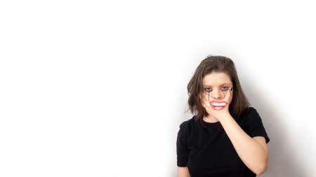 Photo pour Teenage girl 15 yo covering lower part of face with hand, laughing mouth drawn on it, tears painted aqua colors, brown hair loose, black T-shirt.Concept of unspoken feelings, not being yourself.Copy space. - image libre de droit