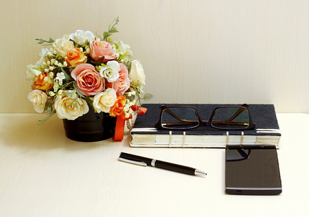 Artificial flowers and set of a black notebook,glasses, pen and smartphone  on wood table blackground.