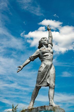Foto für Powerful woman historical monument on blue sky with white clouds background. Social realism stone sculpture in countryside of Ukraine - Lizenzfreies Bild