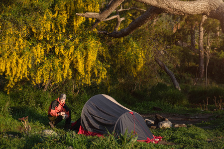 Tourist putting tent and cooking food in a camping in spring forest