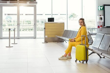 Happy traveler waiting near gates, flight in airport. Woman with yellow suitcase from the back in waiting room